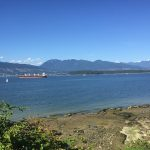 A view of the water of Burrard Inlet from the beach, there is a ship in the distance.