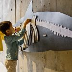 Two young museum visitors complete a puzzle of a harbor porpoise skeleton hanging on a wall.