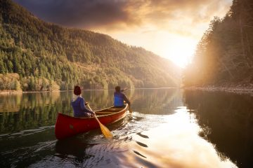 Couple friends canoeing on a wooden canoe during a colourful sunny sunset. Harrison River, BC, Canada. By EB Adventure Photography